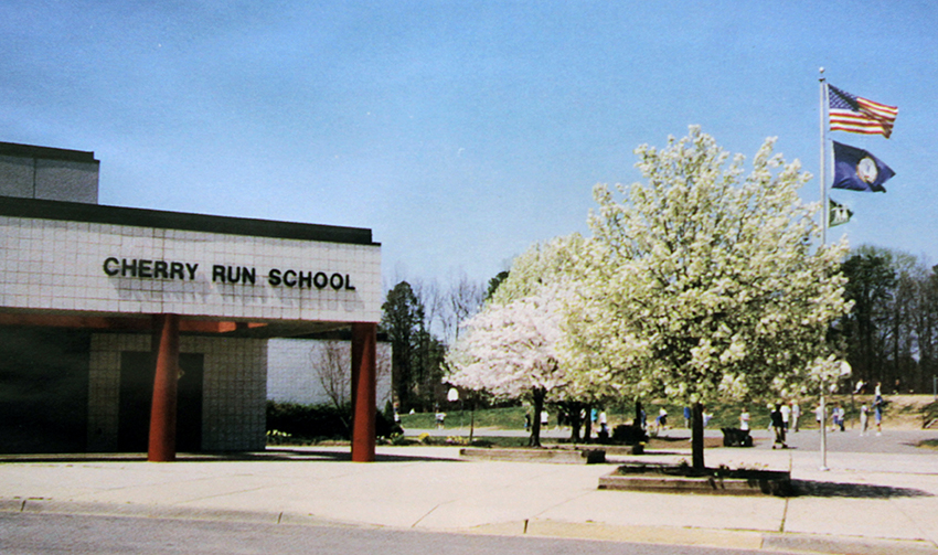 Photograph of the front of Cherry Run Elementary School. The cherry trees are fully grown and are in bloom.