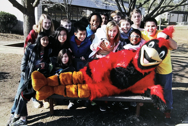 Photograph of Cherry Run's cardinal mascot reclining on a bench in front of the school. The bench is surrounded by smiling students.