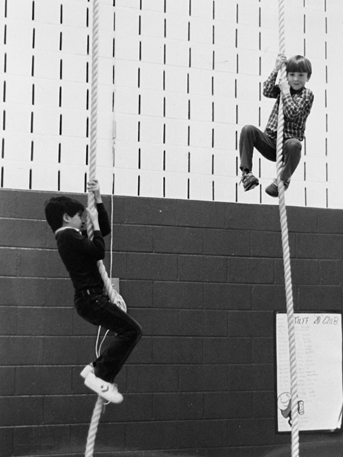 Black and white photograph of two students climbing ropes in the gymnasium.