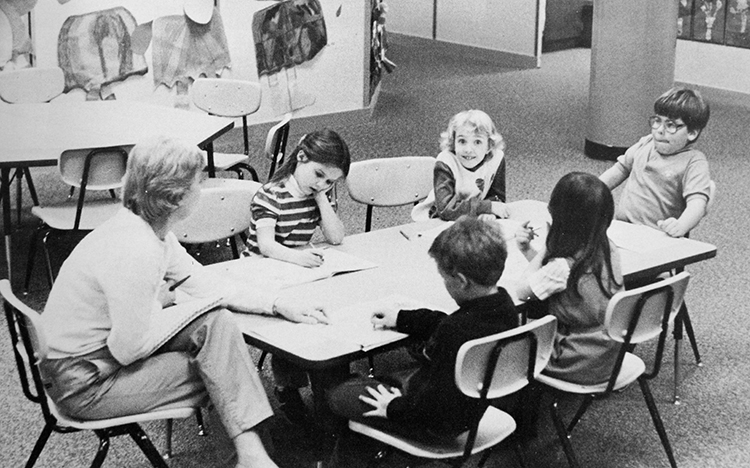 Black and white yearbook photograph of a small group of students working around a table with a teacher.