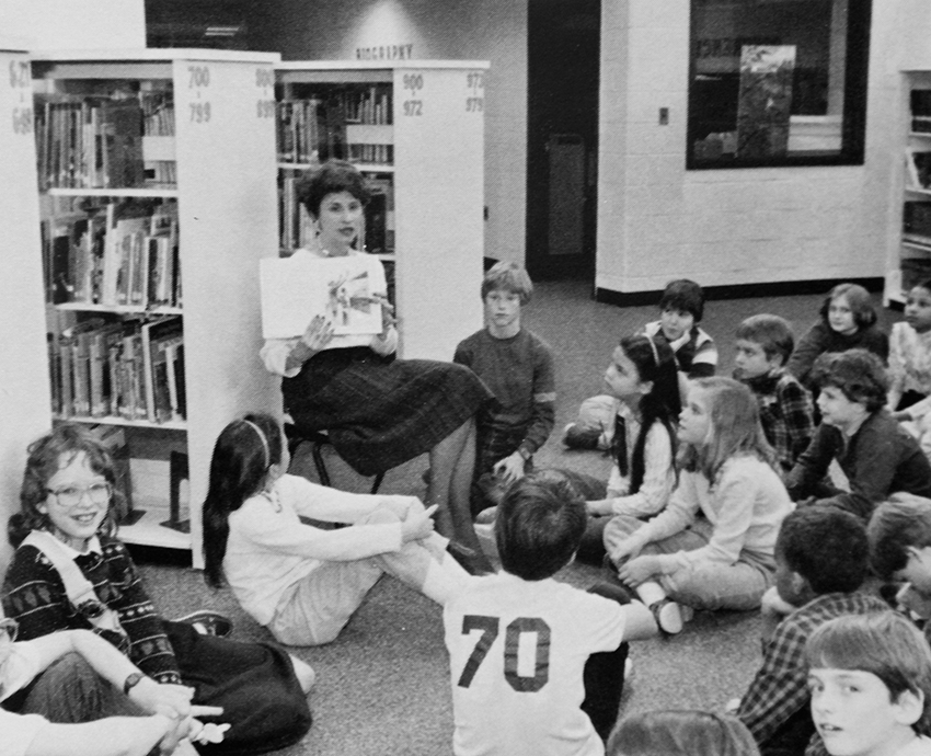 Black and white yearbook photograph of students sitting on the floor in the library. They are looking up at a teacher who is holding open a book and reading it to them.