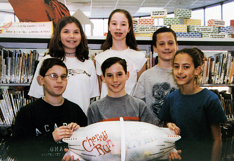 Yearbook photograph of six upper-grade students standing behind a time capsule. The capsule is approximately three feet long, is white in color, and is shaped like a football.